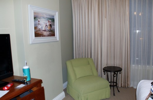 A nice comfy chair, with a side table completes the furnishings in this bedroom.
