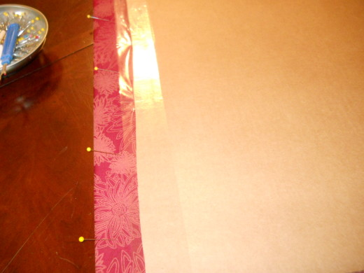 Pin the fabric to the cardboard, then use packing tape