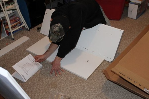 Young Joe reading the instructions while putting the cabinets together.