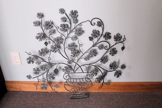 metal wall sculpture of grape vine in a vase