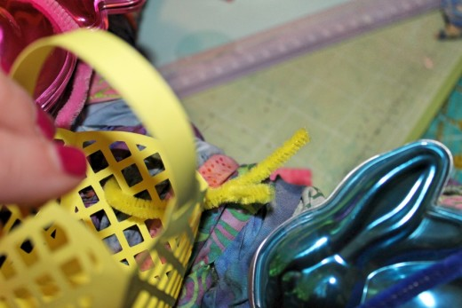 Close up showing pipe cleaner threaded through paper basket.
